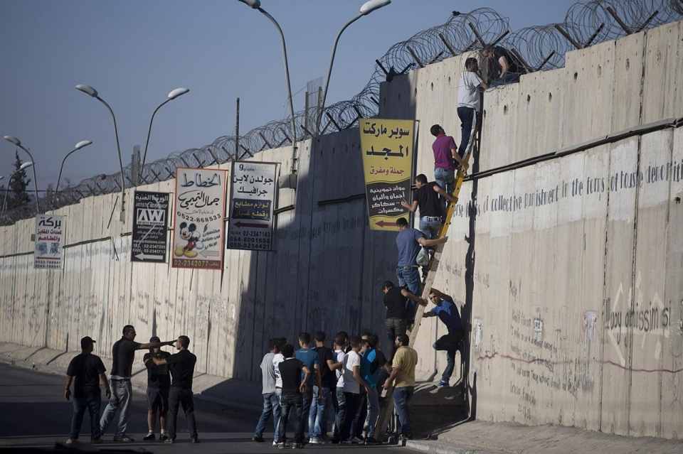 Climbing the wall to attend prayers at Al-Aqsa Mosque, July 26, 2013. Photo by Oren Ziv
