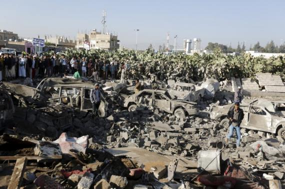 People gather at the site of an air strike at a residential area near Sanaa Airport